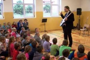Występ nauczyciela śpiewu i wokalu przed dziećmi.