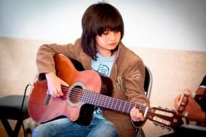 Chłopiec trzymający w rękach gitarę klasyczną.