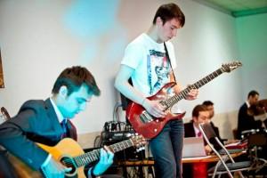 dwóch młodych mężczyzn gra na gitarach