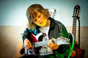 chłopiec uczy się grać na gitarze