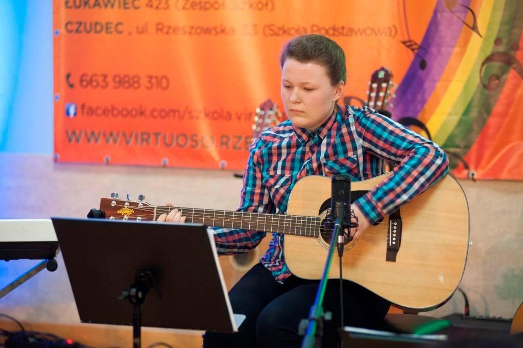 wykonanie utwory na gitarze przez młodą osobę