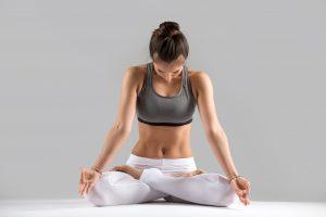 Młoda atrakcyjna kobieta ćwiczy yogę, siedzi w pozycji kwiatu lotosu.