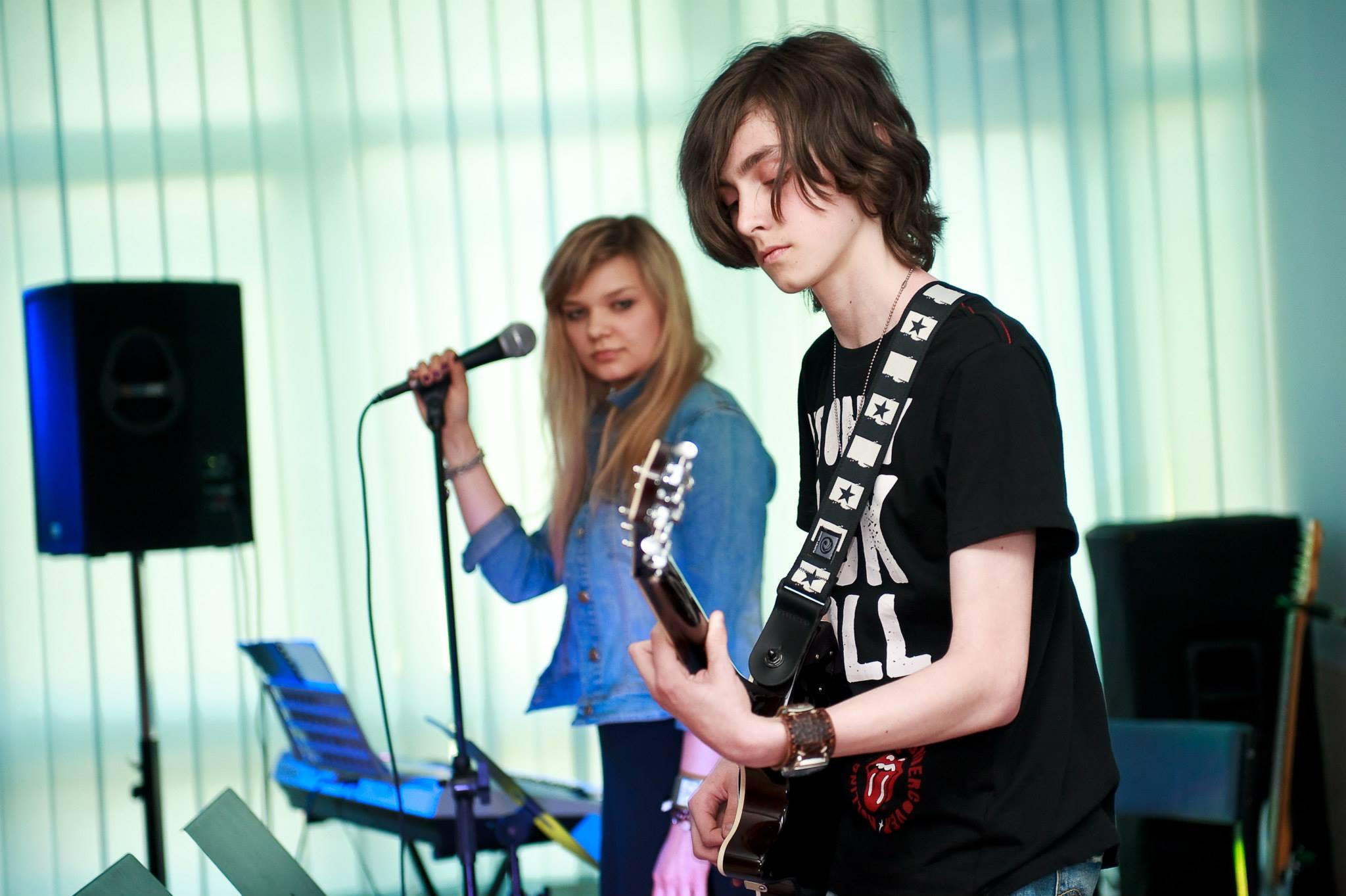 dziewczyna i chłopak gra na gitarze i śpiewa