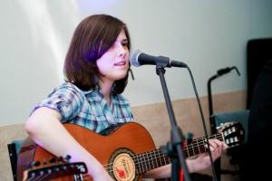 Dziewczynka z gitarą śpiewa do mikrofonu.