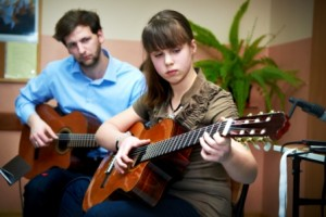 dziewczyna uczy się grać na gitarze akustycznej