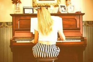 Młoda dziewczyna odwrócona do widza plecami gra na pianinie, które znajduje się w ślicznie ustrojonym pokoju.