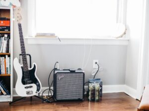 gitara elektryczna w stojaku oraz piecyk