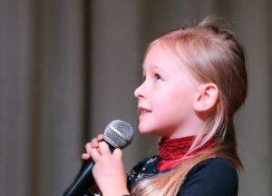 dziewczynka trzyma mikrofon w rękach i przygotowuje się do śpiewu